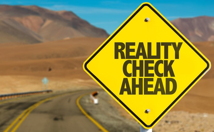 "A ""reality check ahead"" sign on a deserted road."