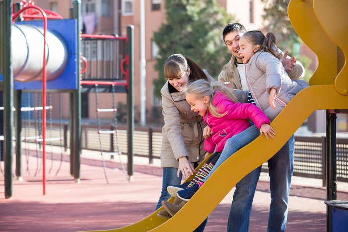Man and woman helping two girls down a slide at a playground.