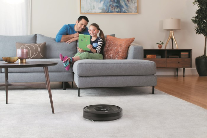 A young girl on a couch, while her father leans over the back, while a robotic vacuum cleans a carpet in the foreground.