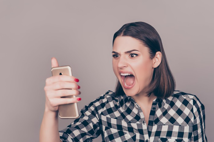 An angry woman screams at her phone.