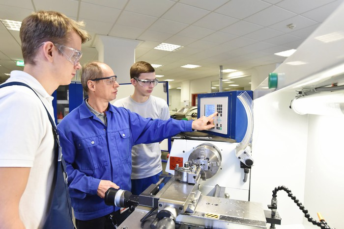 Young recruits being trained on a lathe.