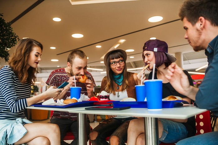 Young adults eating fast food at a mall cafeteria.