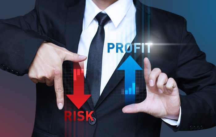 "A man in a suit holding his hands out, framing the words ""RISK"" with an arrow pointing down and ""PROFIT"" with an arrow pointing up"