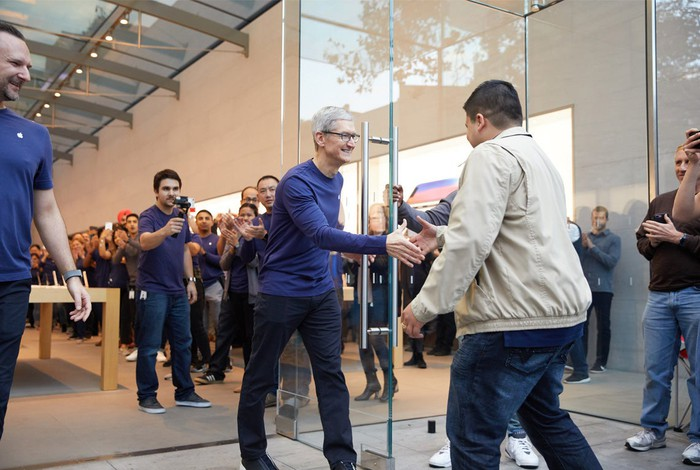 Apple CEO Tim Cook greets a customer at an Apple Store on the iPhone X launch day