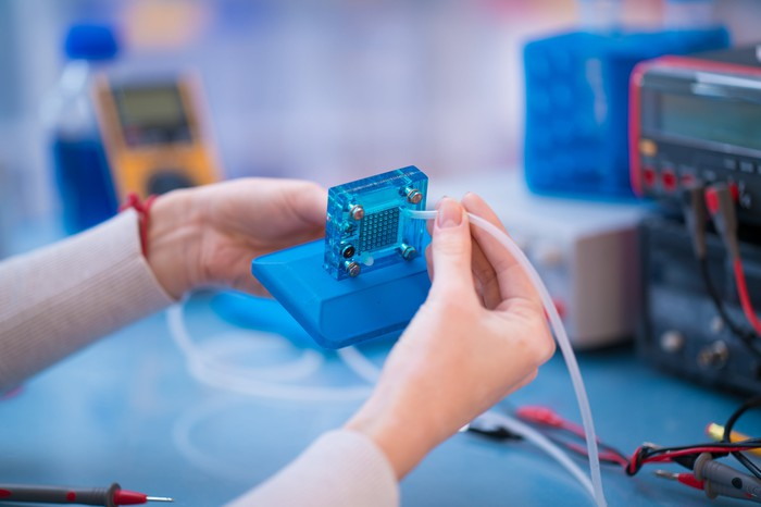 Woman's hands assembling a square fuel cell