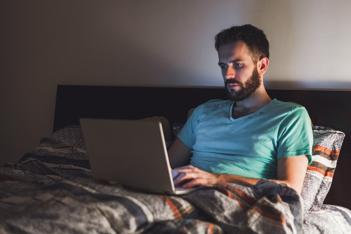 Man using laptop in bed.