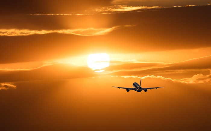 Airplane flying at sunset.
