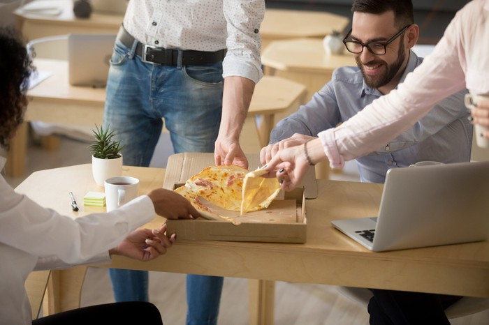 Group of adults sharing a pizza next to a laptop