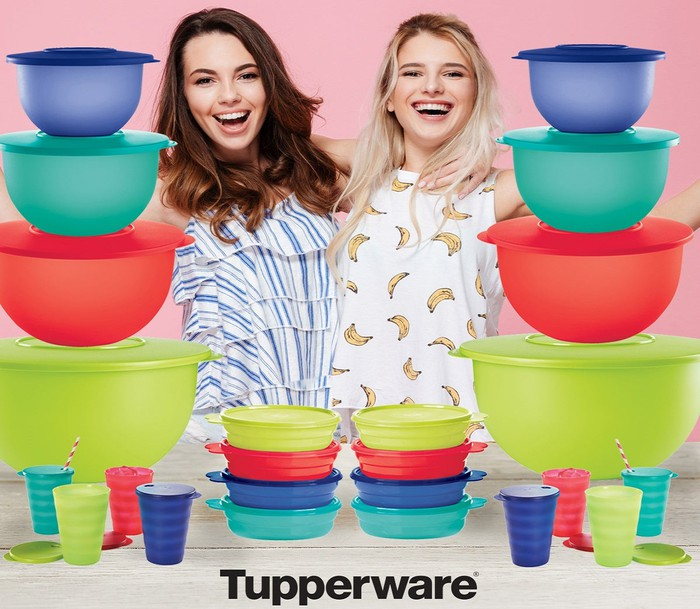 Two women standing next to piled-up Tupperware containers.