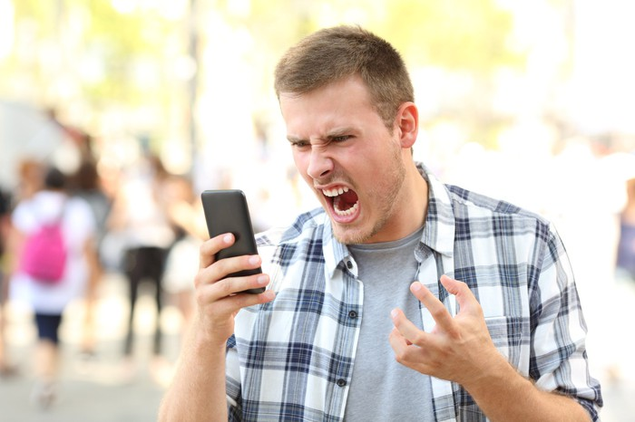 Young man yelling at his smartphone on a crowded street.