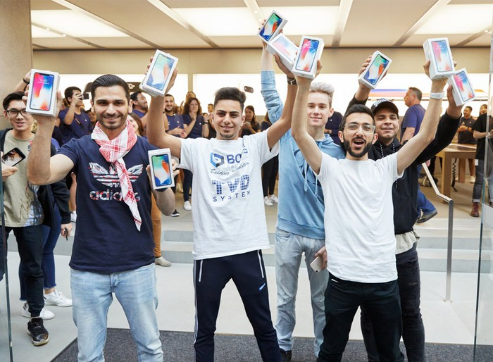 Customers holding up new iPhones in front of an Apple Store