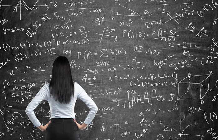 The back of a woman with long brown hair is shown. She has her hands on her hips as she gazes at a huge blackboard full of confusing formulas.