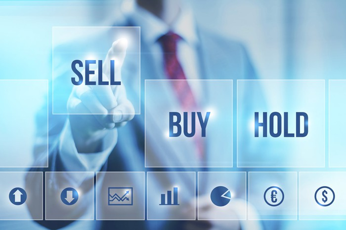 """A businessman in a suit pressing the """"sell"""" button on a digital screen."""