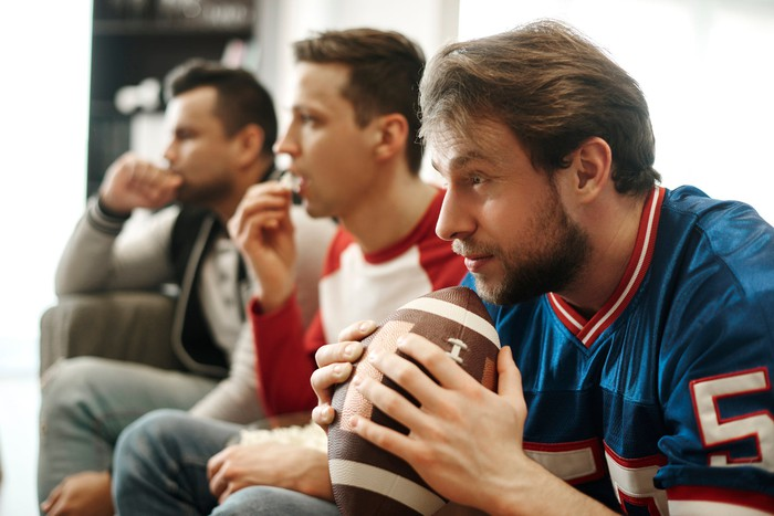 Three men, one of whom is holding a football, intensely watching football on television while seated on the couch.
