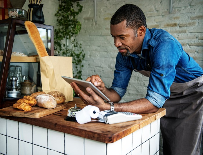 A cafe owner orders supplies on a tablet device.