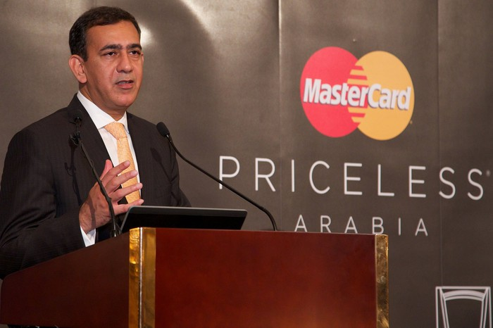 Man in a suit at podium next to Mastercard logo