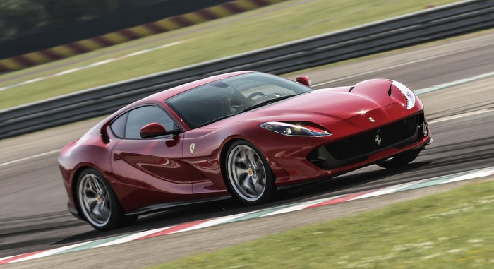 A red 2019 Ferrari 812 Superfast, a two-seat front-engined exotic sports car, at speed on a race track.