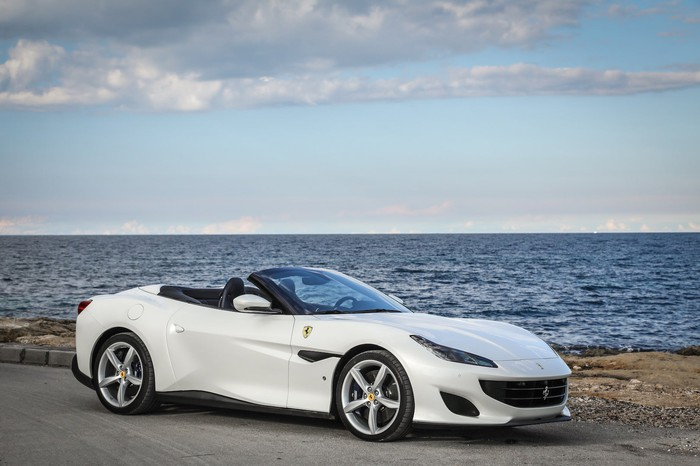 A white Ferrari Portofino, a two-seat front-engined convertible sports car, parked by the ocean.