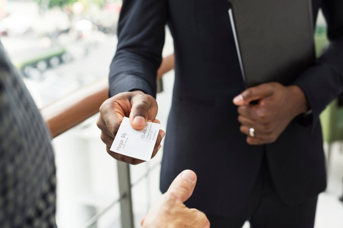 Man in suit handing another person his business card.