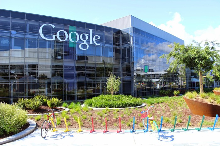Alphabet building with Google text logo on the front and a colorful bike rack in front of the building.