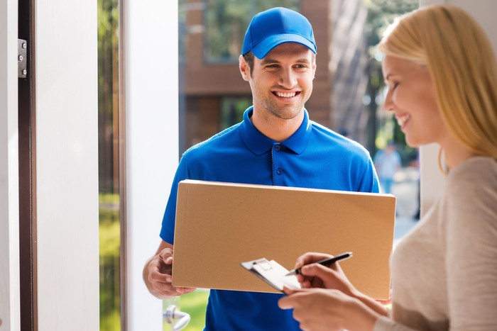 A smiling woman signing for a package being delivered by a man in a blue uniform.