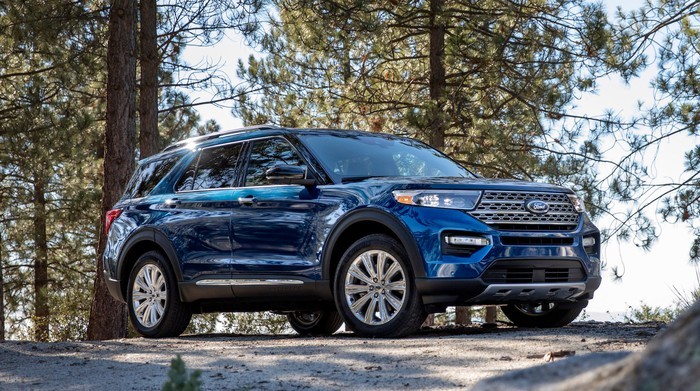 A blue 2020 Ford Explorer, a seven-passenger crossover SUV, parked in a wooded setting