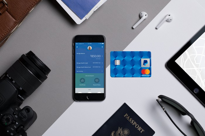 A smartphone and a PayPal branded credit card on a desk surrounded by a camera, passport, sunglasses and earbuds.