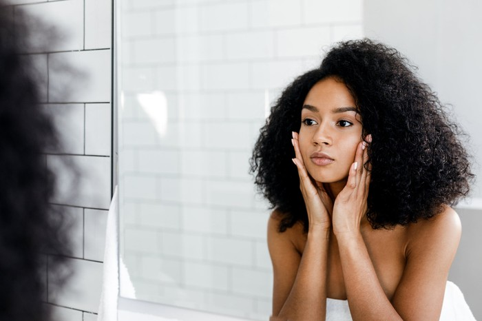 A woman looking in the bathroom mirror and touching her face.