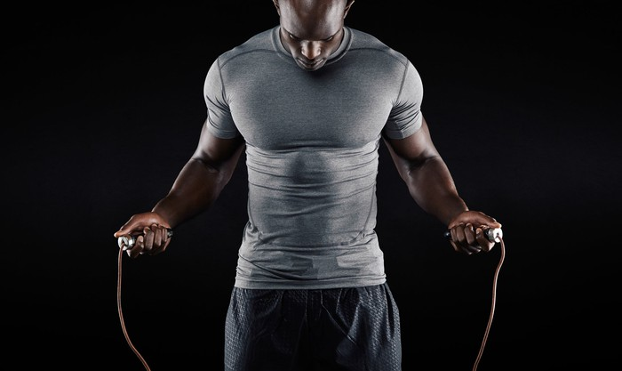 A very fit and muscular man jumping rope.