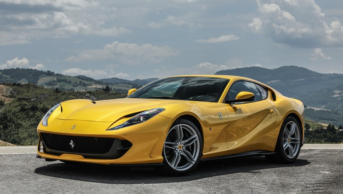 A yellow Ferrari 812 Superfast, a two-seat front-engined sports car, parked on a mountain road.