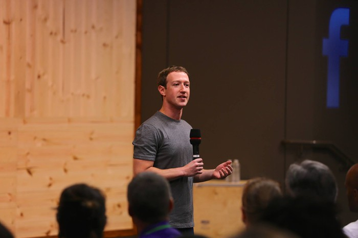 Facebook CEO Mark Zuckerberg holding a microphone and speaking to an audience.