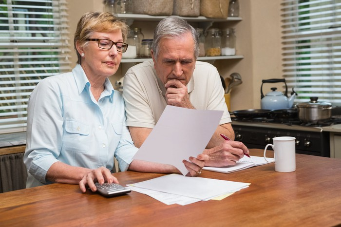 An older couple with a calculator sit at a kitchen table looking concerned at documents.