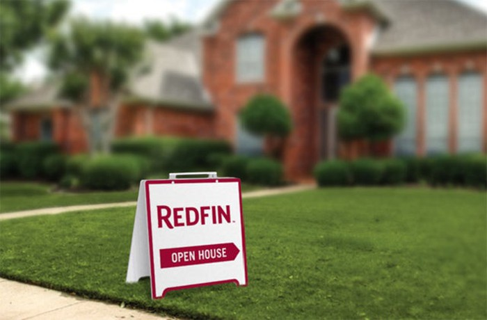 """An """"open house"""" sign with a Redfin logo on the lawn of a home for sale."""