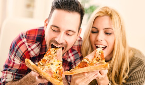 couple eating pizza slices getty