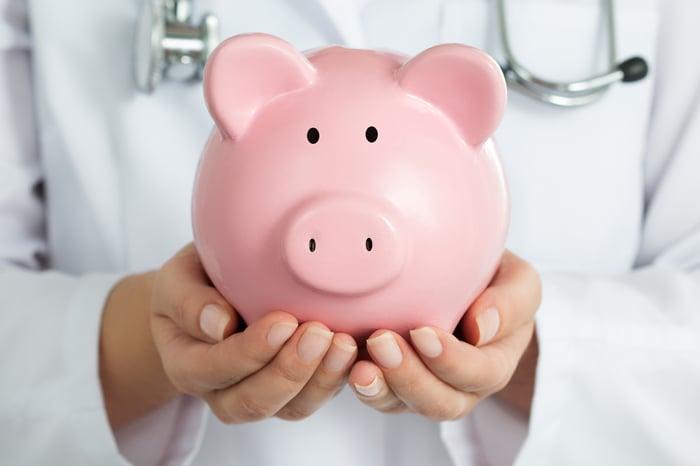 A doctor holding a piggy bank.