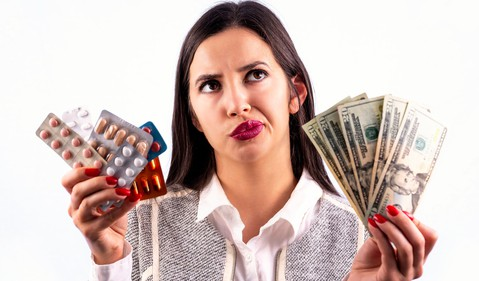 woman holding pills in one hand and money in the other hand