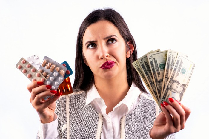 A woman holding money in one hand and pills in the other hand.