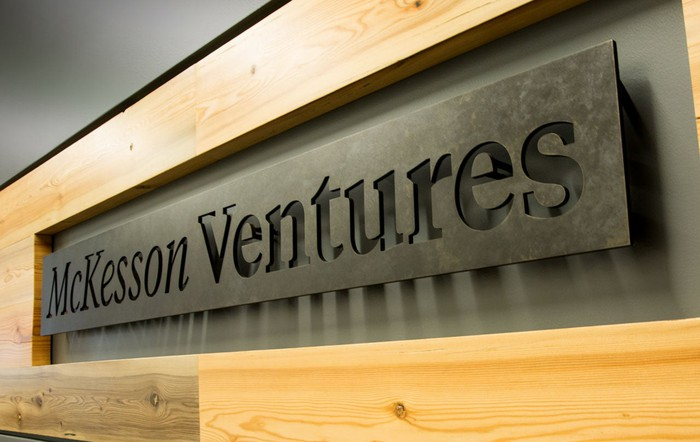 """Metal sign reading """"McKesson Ventures"""" in a wood frame"""