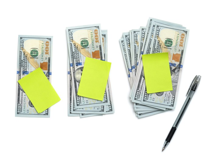 Three stacks of cash with sticky notes on top and a pen lying next to the stacks