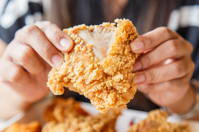 A close-up of a person's two hands breaking a part a piece of fried chicken