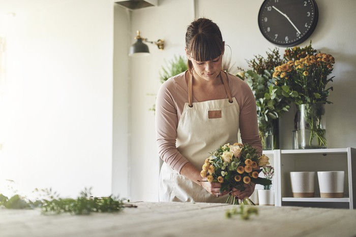 Woman working on floral arrangement