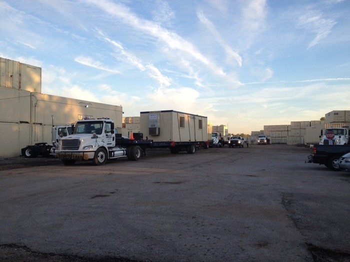 Parking lot with trucks and several Mobile Mini storage containers.