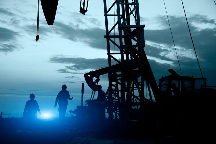 Oil workers near some oil pumps with a bright light in the background.