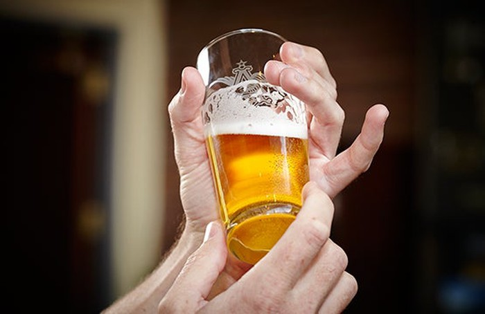 Hand holding a full beer glass