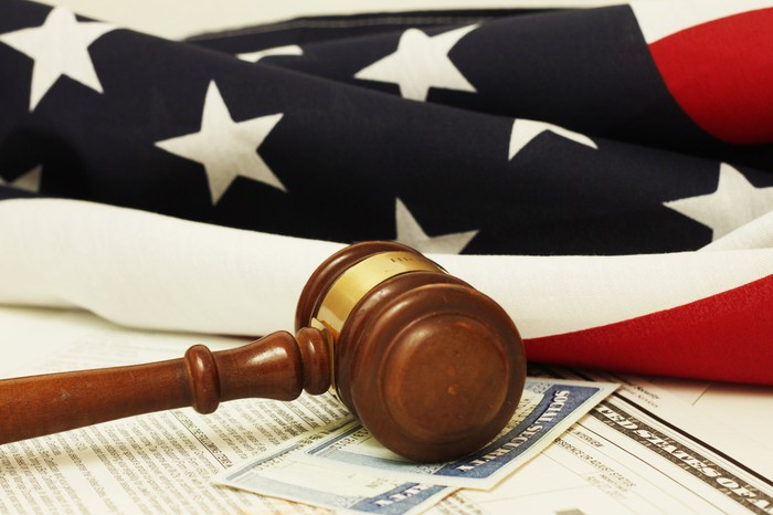 A Social Security card underneath a gavel, with an American flag in the background.