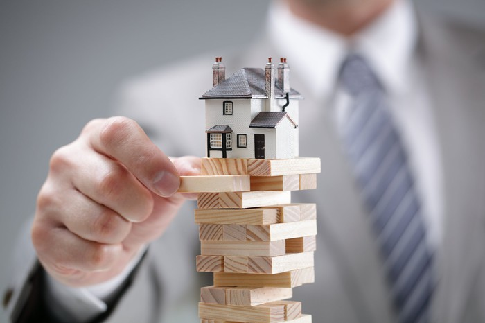 A businessman removing a wooden Jenga block from underneath a miniature house that's teetering above.
