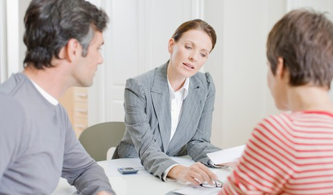 man and woman looking over documents with woman in business suit -- financial advisor planner real estate agent realtor contract