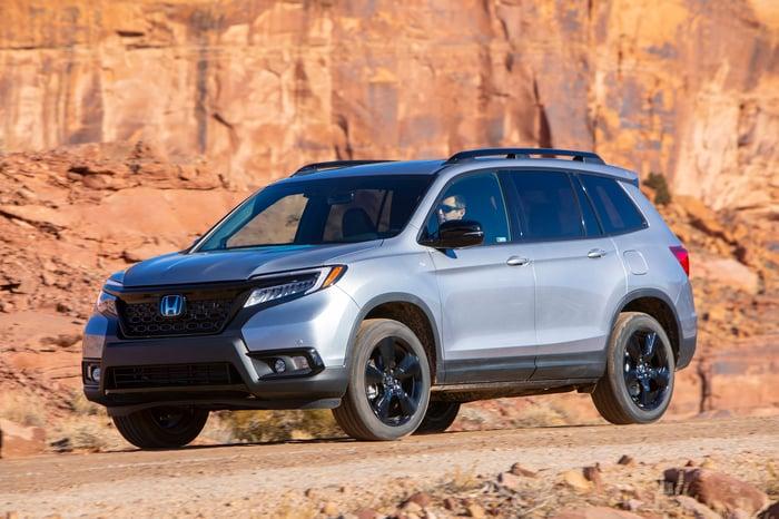 A silver 2019 Honda Passport, a five-passenger midsize crossover SUV, in a desert setting.