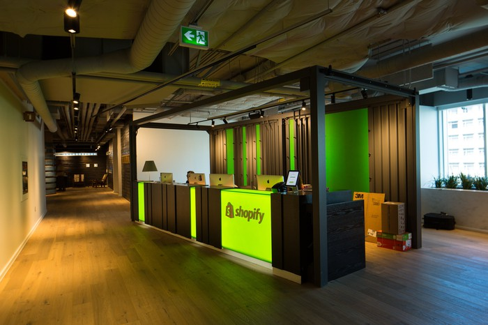 The lobby of Shopify HQ in Ottawa with an illuminated Shopify logo on the front of a desk.