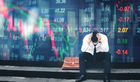 Image 1 An upset businessman sits in front of a screen showing plunging stock prices